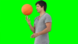 A man practises spinning a basketball on his finge Footage