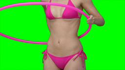 A woman picking up and using a hula hoop Footage