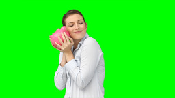 A woman kissing and cherishing her piggybank Footage