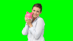 A woman holding her piggybank and kissing it Footage