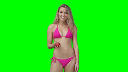 A woman in a bikini holding an apple in hand Stock Video Footage