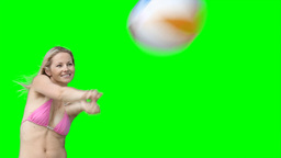 A woman in her bikini passes a beachball back and  Footage