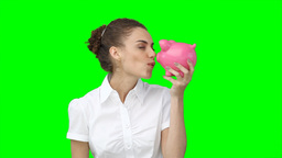 A woman holding her piggybank in her hands as she  Footage