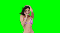 A woman in her bikini dances while smiling Footage