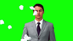 Man in slow motion standing under paper balls Stock Video Footage