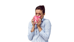 Joyful woman in slow motion kissing a piggy bank Footage