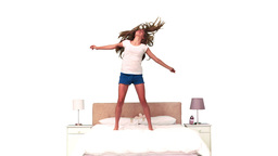Woman bouncing in slow motion on her bed Footage