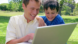 Smiling man using a laptop with his son Footage