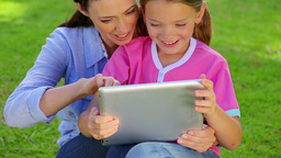 Smiling woman using a tablet pc with her daughter Stock Video Footage