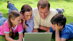 Smiling family lying together while looking at a l Footage