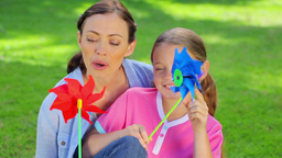 Mother and daughter holding pinwheels Footage
