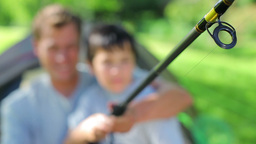 Cheerful father and son using a fishing rod Footage