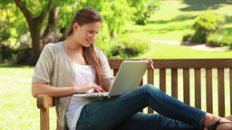 Woman on a bench using a laptop Footage