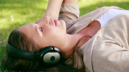 Woman listening to music in a park Footage