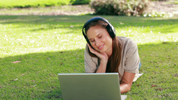 Woman using a laptop is listening to music Stock Video Footage