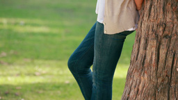 Woman leaning against a tree Footage