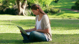 Woman using a laptop while sitting in a park Footage