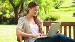 Woman using a laptop on a bench Stock Video Footage