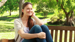 Smiling woman sitting on a bench Stock Video Footage