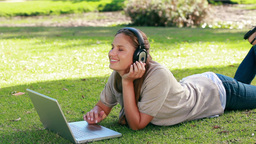 Young woman using a laptop in a park Footage