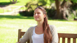 Young woman relaxing on a bench Stock Video Footage