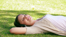 A woman is lying on grass Footage