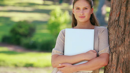 A woman leaning against a tree is holding files Stock Video Footage