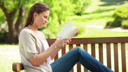 Woman reading a novel while sitting on a bench Footage