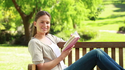 A woman holding a book while sitting on a bench Stock Video Footage