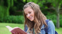 Smiling young woman reading a book Stock Video Footage