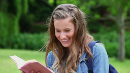 Smiling young woman reading a book Footage