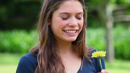 Smiling young woman smelling a flower Footage