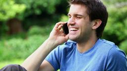 Smiling man sitting while calling Footage