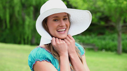 Cheerful young woman holding her hat brim Footage