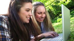 Smiling friends using a laptop Stock Video Footage