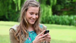 Smiling young woman typing on her cellphone Footage