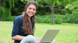 Smiling brunette woman using a laptop Stock Video Footage
