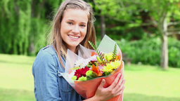 Happy young woman holding a bunch of flowers Footage