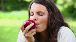 Joyful woman eating a red apple Stock Video Footage