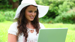 Smiling brunette woman using her laptop Footage