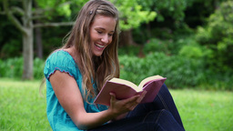 Smiling woman reading a fascinating novel Stock Video Footage