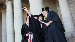 Graduated students taking themselves in picture Footage