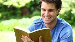 Smiling man reading a fascinating book Footage