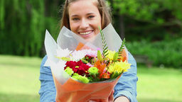Happy woman holding a bunch of flowers Footage