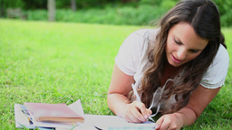 Brunette woman writing on notebooks Footage