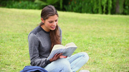 Smiling brunette attentively reading a book Footage