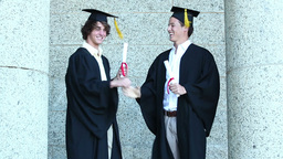 Two graduates giving highfive Footage