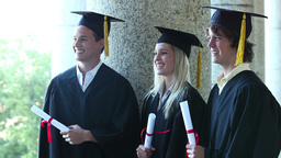 Three graduates laughing together Stock Video Footage
