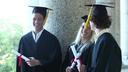 Three graduates laughing together Footage