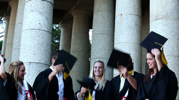 Graduates students throwing mortar boards in the a Footage
